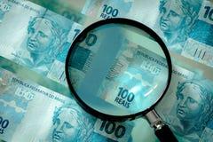 与放大镜的巴西金钱,一百雷亚尔钞票 免版税库存照片