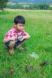 年轻与放大镜的男孩探索的自然 户外在Th 图库摄影
