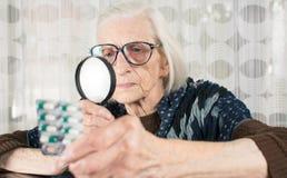 与放大镜的资深妇女读书药片名字 库存照片