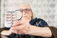 与放大镜的资深妇女读书药片名字 免版税库存照片
