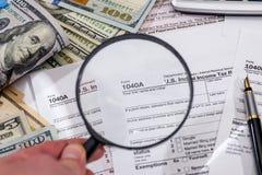 1040与放大镜美元的报税表,笔 库存图片