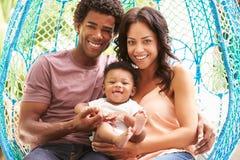 与放松在室外庭院摇摆位子的婴孩的家庭 库存图片