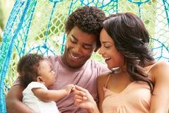 与放松在室外庭院摇摆位子的婴孩的家庭 免版税库存图片