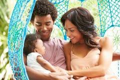 与放松在室外庭院摇摆位子的婴孩的家庭 免版税库存照片