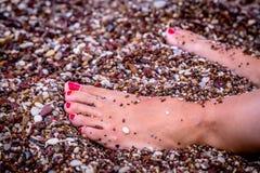 与放松在小卵石的一个少妇的红被绘的钉子的脚在希腊靠岸 免版税库存图片