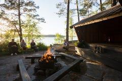 与放松在森林里的朋友的木灼烧的Firepit 免版税库存图片