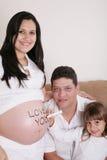 与放松在沙发的怀孕的母亲的家庭与w一起 免版税库存图片