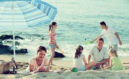 与放松在海滩的四个孩子的家庭 库存照片