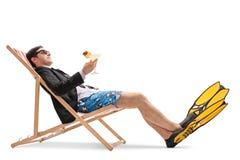 与放松在轻便折叠躺椅的飞鱼的商人 免版税库存图片