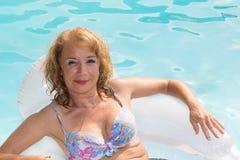 与放松在水池的成人中年妇女的暑假图象 库存照片