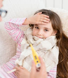 与放置在床和母亲上的高烧的病的孩子采取温度 免版税库存照片