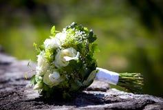 与放置在石灰石墙壁的黄色玫瑰的婚礼花束 库存图片