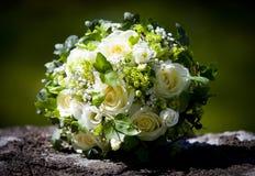 与放置在石灰石墙壁的黄色玫瑰的婚礼花束 免版税库存图片
