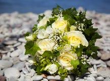 与放置在石灰石海滩的黄色玫瑰的婚礼花束 库存照片