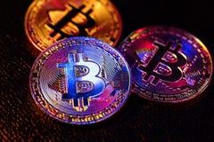与放置在黑背景的bitcoin商标的三枚硬币 免版税库存照片