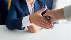 与政客握手和给他贿款的人的特写镜头图象 免版税库存照片