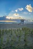 与救生员立场和沙丘的佛罗里达日出 库存图片