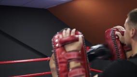 与教练的有动机的kickboxer训练在拳击爪子,使用拳击露指手套 为竞争做准备 冒汗的面孔 股票视频