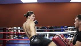与教练的Kickboxer训练在拳击爪子,使用拳击露指手套 为竞争做准备 冒汗的面孔,赤裸上身 股票视频