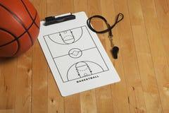 与教练的剪贴板和口哨的篮球在木地板上 图库摄影