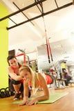 与教练的少妇训练在健身房 免版税图库摄影