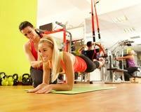 与教练的少妇训练在健身房 免版税库存照片