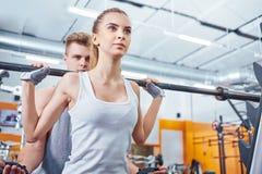 与教练的年轻,美好的女孩训练在健身房 库存照片