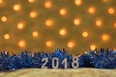 与数值的蓝色闪亮金属片2018年在桌在一本新年` s诗歌选的背景有金黄光的 免版税库存图片