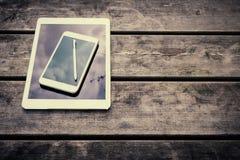 与数字式片剂和智能手机的土气木桌 在视图之上 免版税库存照片