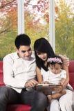 与数字式片剂的可爱的家庭在家 免版税库存照片