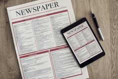 与数字式片剂的报纸在木背景 免版税图库摄影