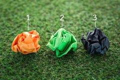 与数字的三个五颜六色的纸垃圾球在绿草 JPG 免版税库存图片