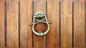 与敲圆环的葡萄酒古铜色瘤 在葡萄酒古铜色门把手的特写镜头与敲在棕色木背景的圆环 库存图片