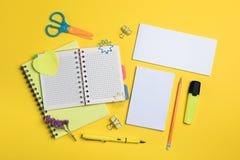 与文具的平的被放置的构成在黄色背景 嘲笑为设计 免版税库存图片