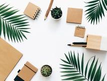 与文具集合、供应和棕榈叶的最小的办公桌桌 顶视图 库存照片