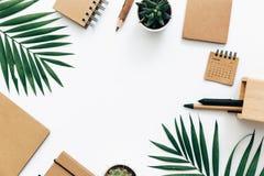 与文具集合、供应和棕榈叶的最小的办公桌桌 库存图片