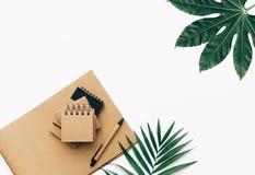 与文具集合、供应和棕榈叶的最小的办公桌桌 免版税库存照片