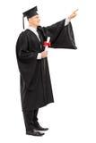 与文凭的指向男性的大学毕业生  免版税库存照片