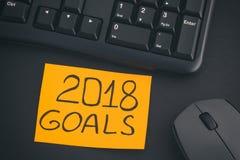 与文字2018目标的纸笔记在有黑键盘的一张书桌上 库存照片