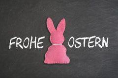 与文本'在黑板背景的Frohe Ostern的'桃红色复活节兔子 翻译:'复活节快乐' 库存图片