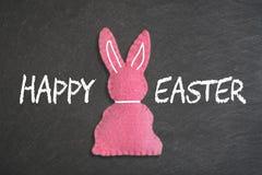 与文本'复活节快乐的'桃红色复活节兔子在黑板背景 免版税库存照片