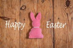 与文本'愉快东部的'桃红色复活节兔子在木背景 库存照片