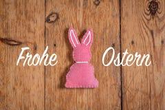 与文本'Frohe Ostern'和木背景的桃红色复活节兔子 翻译:'复活节快乐' 免版税库存图片