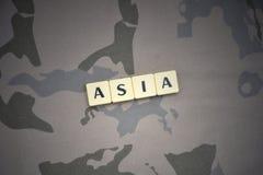 与文本亚洲的信件在卡其色的背景 装甲攻击机体关闭概念标志绿色m4a1军用步枪s射击了数据条工作室作战u 免版税库存照片