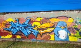 与文本元素和恼怒的企鹅的五颜六色的街道画 免版税库存照片
