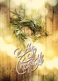 与文本圣诞快乐的贺卡在从绿色自然花圈的背景 轻的Boke 定调子 免版税库存照片
