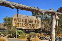 与文本欢迎的老木牌到Hillsboro 垂悬在分支 库存图片