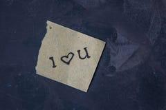 与文本的笔记我爱你在黑暗的背景 免版税图库摄影
