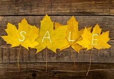 与文本销售的秋叶在土气木背景 秋天 图库摄影