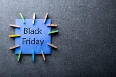 与文本黑色在它写的星期五的一个蓝纸标签反对深灰背景 与最大的销售的天 免版税库存图片